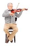 Hög gentleman som spelar en fiol som placeras på en stol Royaltyfri Fotografi