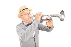 Hög gentleman som spelar en trumpet Royaltyfri Foto