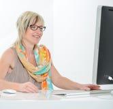 Hög härlig ung kvinna som arbetar på kontoret med datoren Arkivfoto