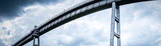 Hög järnstångbro Dramatisk panorama- bakgrund Arkivbild