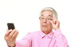 Hög japansk man med presbyopia Fotografering för Bildbyråer