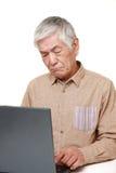 Hög japansk man som använder datoren som ser förvirrad royaltyfri foto