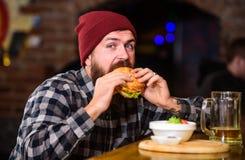 Hög kalorimat Fuskmål Läckert hamburgarebegrepp Tyck om smak av den nya hamburgaren Äter den hungriga mannen för hipsteren hambur royaltyfria bilder