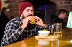 Hög kalorimat Läckert hamburgarebegrepp Tyck om smak av den nya hamburgaren Äter den hungriga mannen för hipsteren hamburgaren up royaltyfri bild