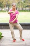 Hög kinesisk kvinna som gör Tai-Chi i Park Arkivbild