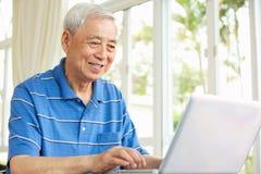 Hög kinesisk man som sitter genom att använda bärbar dator hemma arkivfoto