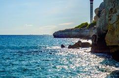 Hög klippa bakgrund ovanför för havet som, sommarhav är många plaska Arkivbild