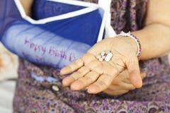 Hög kvinna för bruten arm som tar hennes preventivpillerar Arkivfoton
