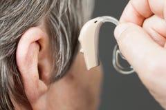 Hög kvinna för Closeup som använder hörapparat royaltyfri foto