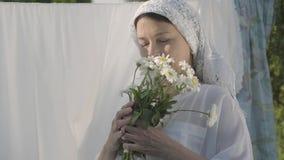 Hög kvinna för stående med den vita sjalen på hennes huvud som sniffar tusenskönor som utomhus ser kameran nära klädstrecket arkivfilmer