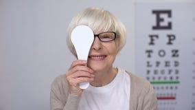 Hög kvinna i anblickar som stänger ögat och ler, riktig linsdiopter, undersökning lager videofilmer