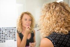 Hög kvinna i badrum med makeup för lockiga hår royaltyfri foto