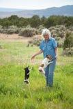 Hög kvinna i ett fält med hennes hundkapplöpning fotografering för bildbyråer