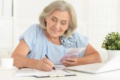 Hög kvinna i hörlurar som sitter på tabellen med bärbara datorn royaltyfria foton