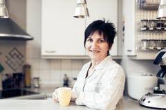 Hög kvinna i kök Arkivbild