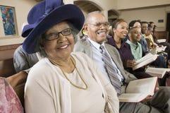 Hög kvinna i söndag som är mest bra bland kongregationen på den kyrkliga ståenden royaltyfria foton