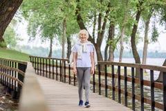 hög kvinna i sportswear som går på träbanan arkivfoton