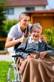 Hög kvinna i vårdhem med sjuksköterskan i trädgård Fotografering för Bildbyråer