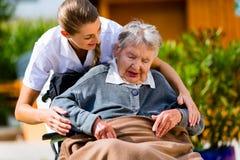 Hög kvinna i vårdhem med sjuksköterskan i trädgård Royaltyfria Bilder