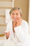 Hög kvinna med ansiktsbehandlingkräm i badrum fotografering för bildbyråer