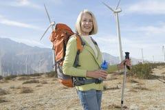 Hög kvinna med att fotvandra Pole och ryggsäcken på Windfarm Royaltyfria Bilder