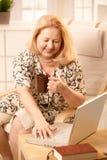 Hög kvinna med bärbar dator Royaltyfria Bilder