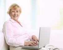 Hög kvinna med bärbara datorn. Arkivbilder