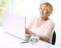 Hög kvinna med bärbara datorn. Royaltyfri Foto