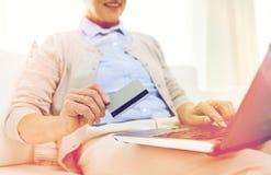 Hög kvinna med bärbara datorn och kreditkorten hemma Arkivbild