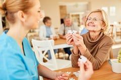 Hög kvinna med demens som spelar pusslet royaltyfri bild