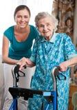 Hög kvinna med den hem- anhörigvårdaren Arkivfoton