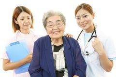 Hög kvinna med den medicinska personalen Arkivbild