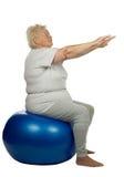 Hög kvinna med en fitboll Arkivfoto