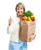 Hög kvinna med en livsmedelsbutikshoppingpåse. Fotografering för Bildbyråer