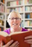 Hög kvinna med exponeringsglasavläsningsboken hemma Royaltyfri Bild