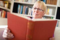 Hög kvinna med exponeringsglasavläsningsboken hemma Arkivbild