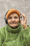 Hög kvinna med hörlurar som lyssnar till musik Arkivfoto