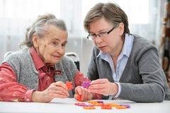 Hög kvinna med hennes äldre omsorgsjuksköterska