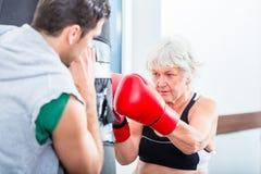 Hög kvinna med instruktören, i att munhuggas för boxning Royaltyfri Fotografi