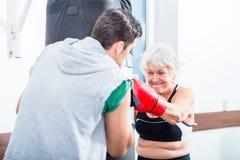 Hög kvinna med instruktören, i att munhuggas för boxning Royaltyfri Foto