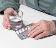 Hög kvinna med preventivpillerar och exponeringsglas av vatten hemma Fotografering för Bildbyråer