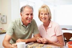 Hög kvinna med stekheta kakor för make i kök fotografering för bildbyråer