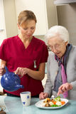 Hög kvinna med vårdare som hemma äter mål Royaltyfri Foto