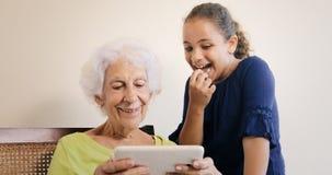 Hög kvinna och barnbarn med minnestavladatoren för internet royaltyfri bild
