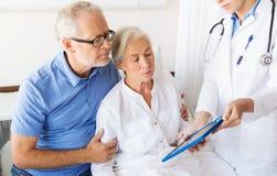 Hög kvinna och doktor med minnestavlaPC på sjukhuset Royaltyfri Bild