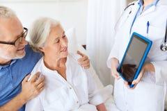 Hög kvinna och doktor med minnestavlaPC på sjukhuset Arkivfoto
