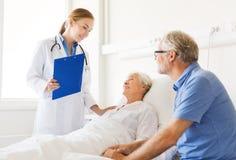 Hög kvinna och doktor med skrivplattan på sjukhuset Royaltyfri Foto