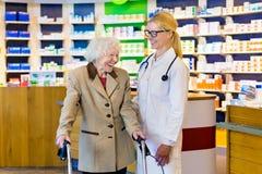 Hög kvinna och doktor som skrattar i apotek royaltyfria bilder