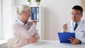 Hög kvinna och doktorsmöte på sjukhuset lager videofilmer