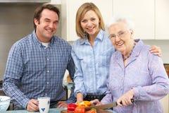 Hög kvinna och familj som tillsammans förbereder mål royaltyfria foton